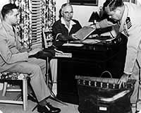 Truman at his desk with the 'buck stops here' sign