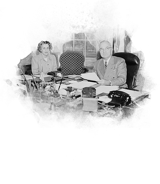 President Truman and his secretary at the President's desk in the Oval Office signing the National Security Act